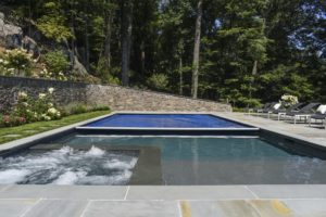 Savings from an automatic pool cover. Royal blue automatic pool cover is halfway covering a large in-ground pool.
