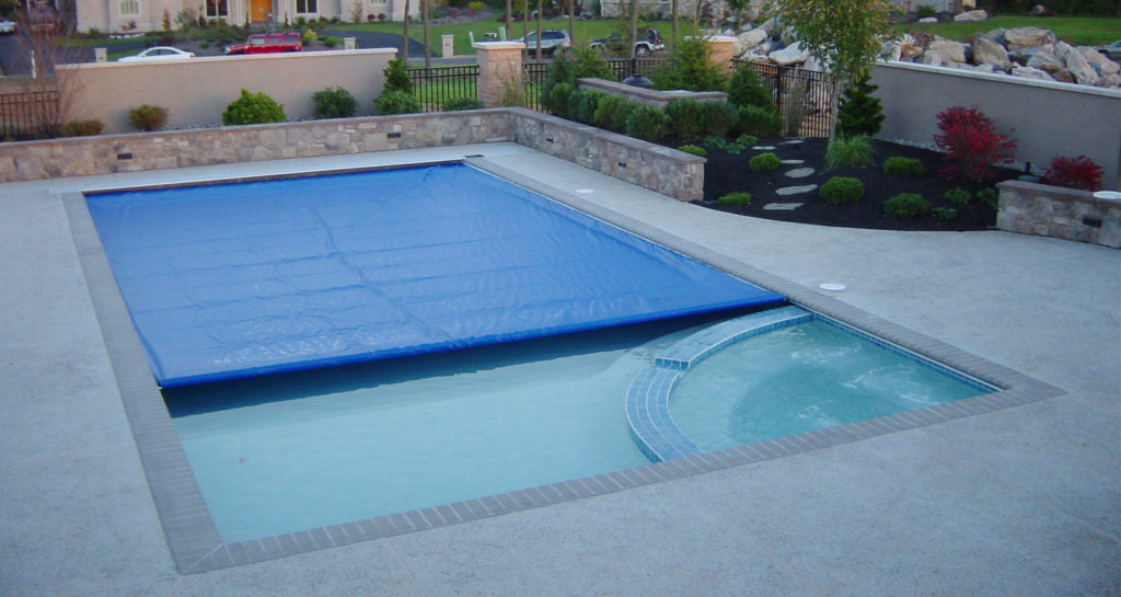 A light blue undertrack guide automatic pool cover is shown 3/4 closed.